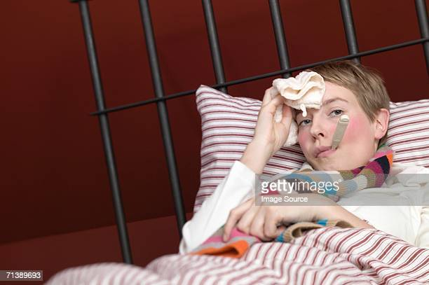 Woman with cold lying in bed