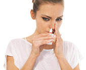 Woman with cold using nasal spray
