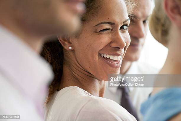 Woman with colleagues, winking playfully at camera