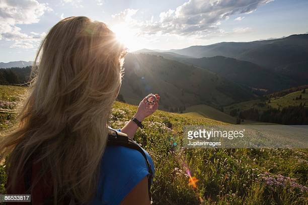 Woman with compass on mountainside