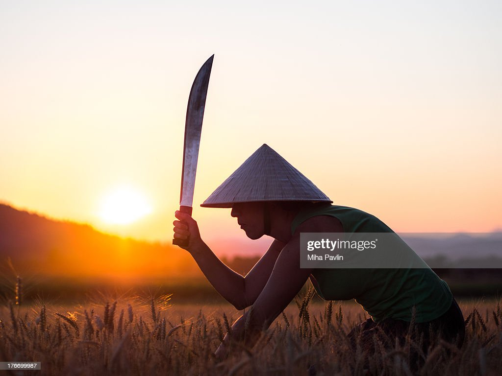 Woman with conical hat and machete at sunset