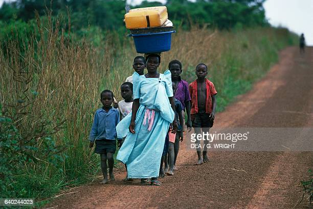 Woman with containers on her heads leading kids along a Kabalega road or Murchison Falls national park Uganda
