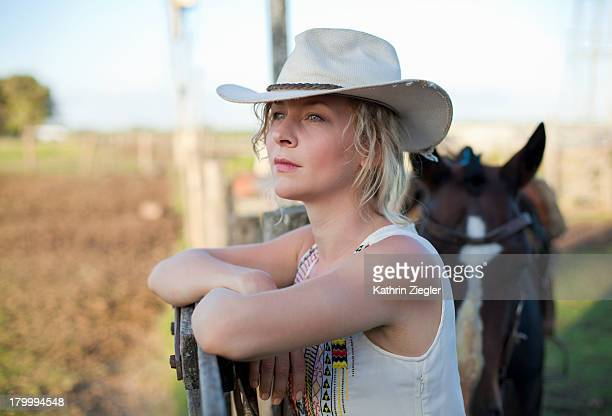 woman with cowboy hat and horse leaning on fence