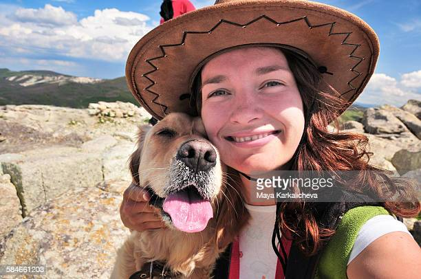 Woman with cowboy hat hugging golden retriever dog