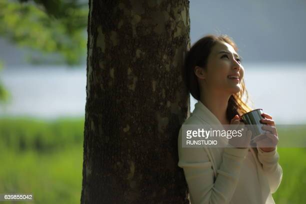 woman with cup coffee enjoying near riverside against a tree