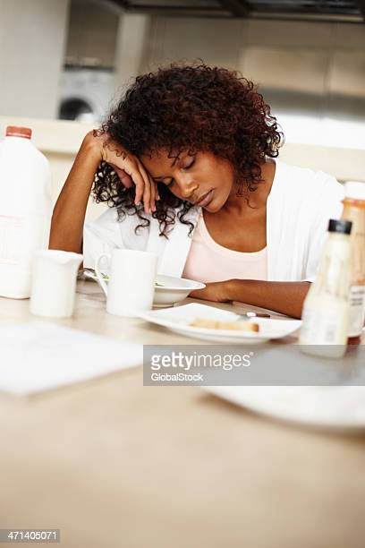 A woman with curly hair asleep at a table