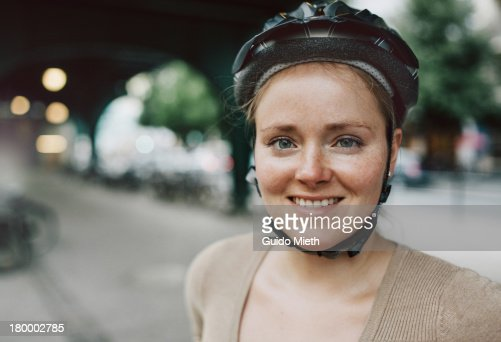 Woman with cycling helmet in a urban scene.