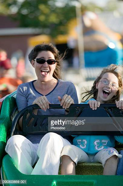 Woman with daughter (6-7) riding on rollercoaster