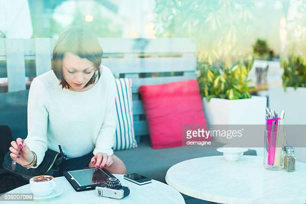 Femme avec appareil pendant une pause-café