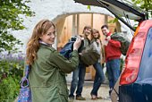 Woman with digital camera photographing friends