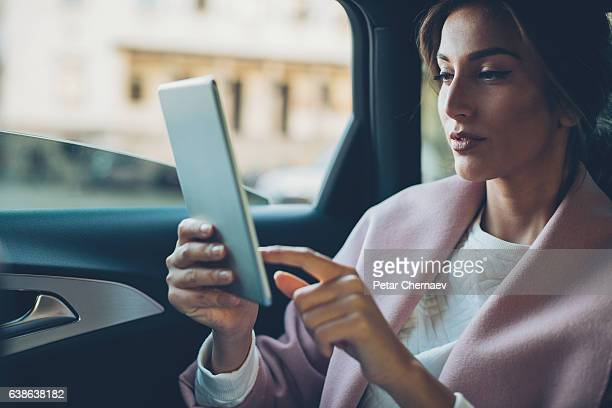 Woman with digital tablet in a car