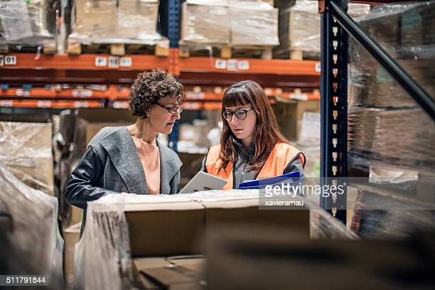 Woman with digital tablet in warehouse talking to worker