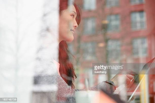 Woman with digital tablet looking out of glass window