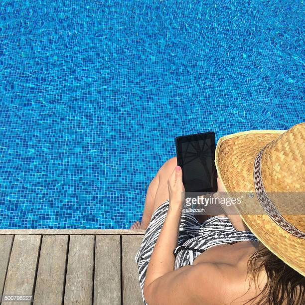 Woman with digital tablet sitting at the edge of swimming pool