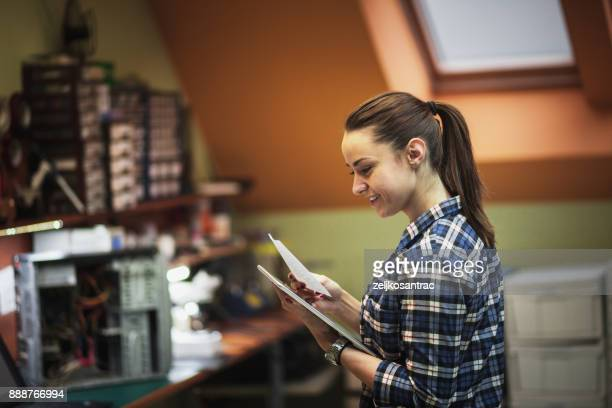 woman with digital tablet surrounded by tools in workshop