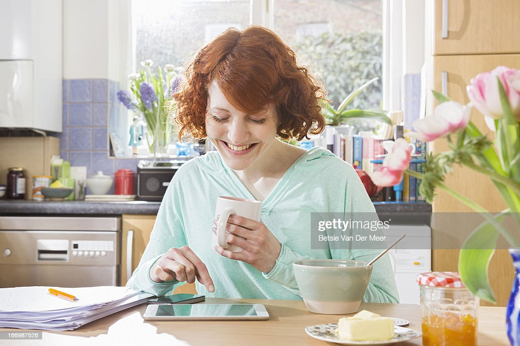 Woman with digital tablet while having breakfast. : Stock Photo