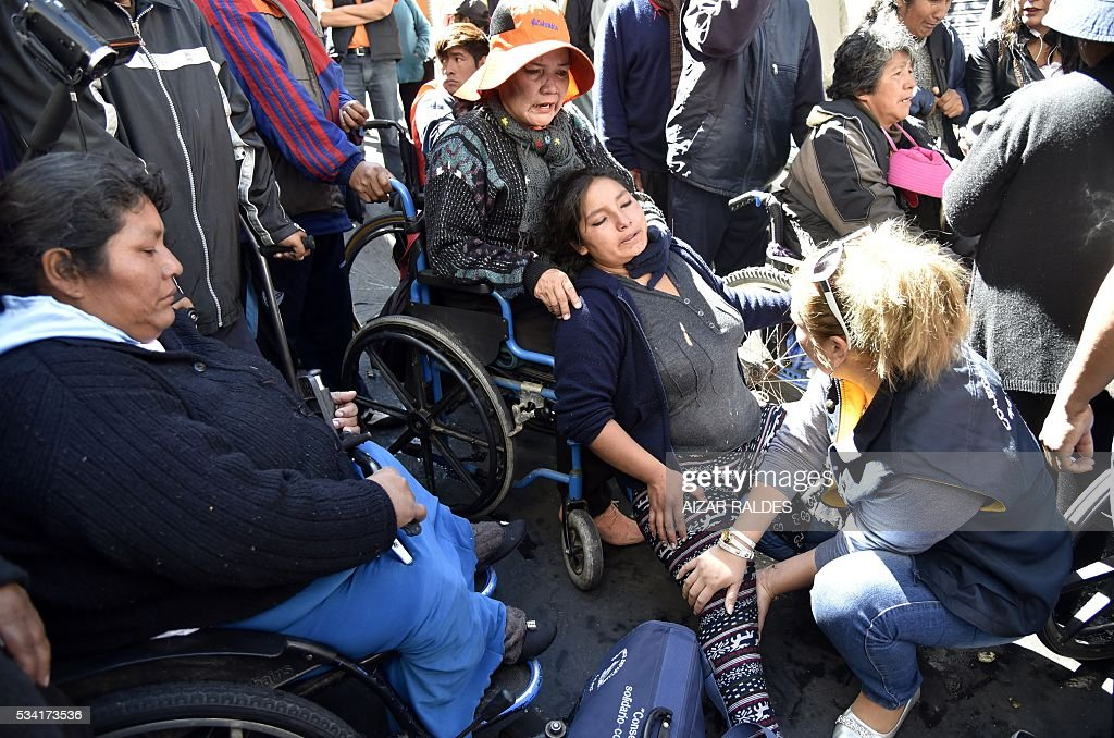 A woman with disabilities is assisted as they are prevented by the riot police from reaching the presidential palace in La Paz to protest in demand of a raise in the subsidy for the disabled, on May 25, 2016. People with disabilities have been staging protests for almost a month demanding the government of Bolivian President Evo Morales that their benefit -- currently at 80 Bolivian pesos (about 11 US dollars) -- is raised to 500 pesos (about 72 US dollars). / AFP / AIZAR