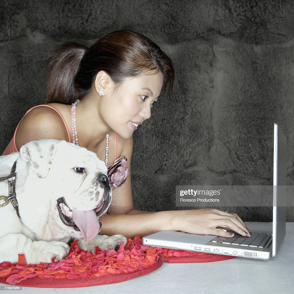 Woman with dog and laptop indoors : Stock Photo
