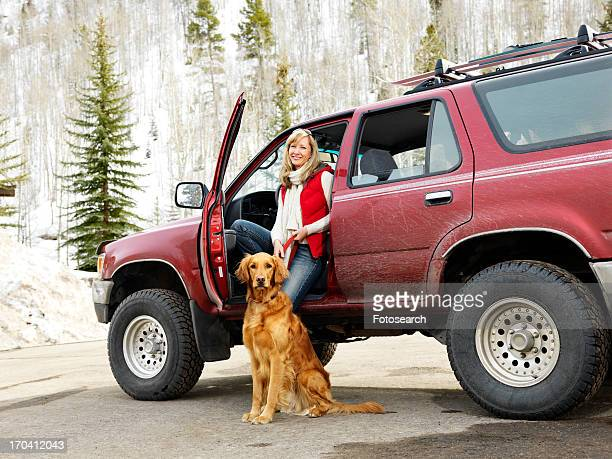Woman with dog sitting with dirt splattered SUV