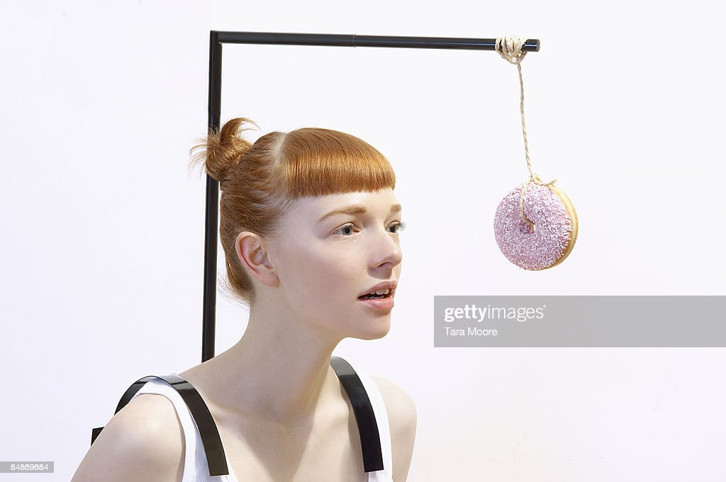 woman with donut dangling in front of face : Stock Photo