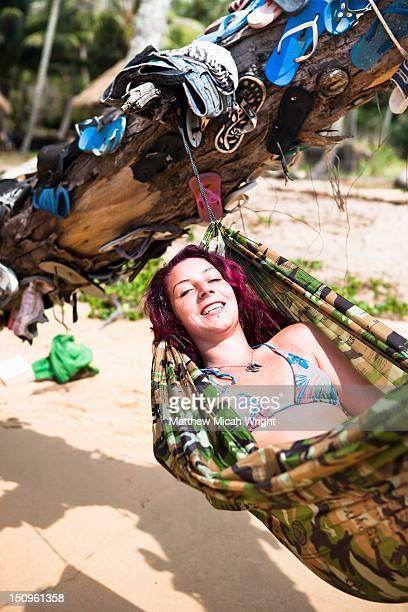 A woman with dreadlocks sits in a hammock.