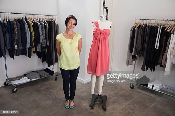 Femme avec une robe sur un mannequin dans la boutique