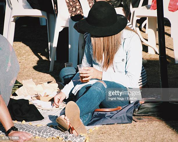 Woman With Drink Sitting On Field During Sunny Day