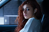 Redhead Woman with Earbuds Sitting in a Car