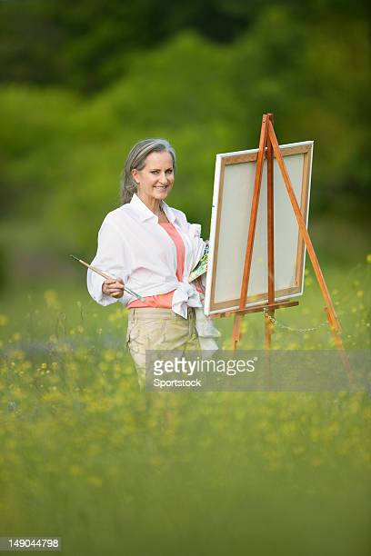 Woman With Easel In Field Of Wildflowers