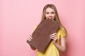 Woman with chocolate smiling. Cute girl holding and eating giant cocoa chocolate bar near pink wall.