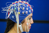 Picture of a young woman with electrodes in her head to record psychophysiological signals for research purposes. Electrocardiogram (ECG), electroencephalogram (EEG) and electrooculogram (EOG) being r