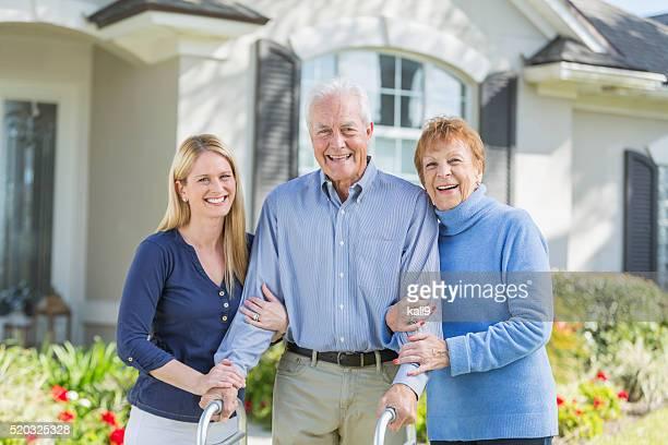 Femme avec vieux parents se tenant debout dans à l'avant de l'hôtel