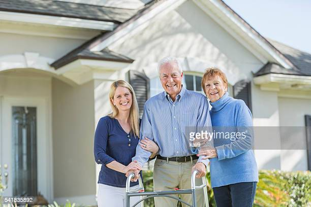 Woman with elderly parents standing in front of house