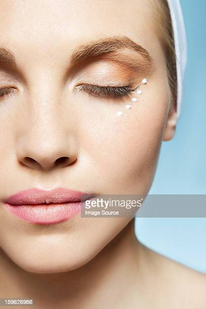 Woman with eye cream around eye