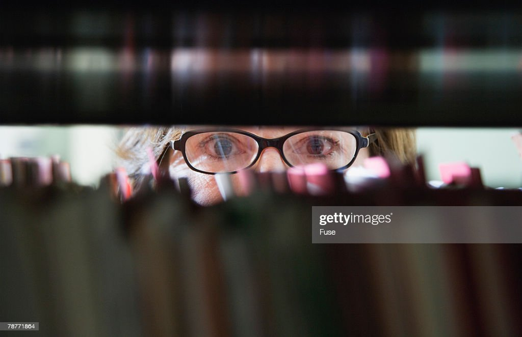 Woman with Eyeglasses Behind File Cabinet