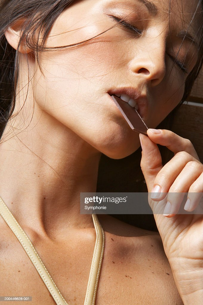 Woman with eyes closed and eating chocolate, close-up : Stock Photo