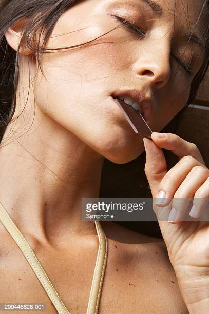 Woman with eyes closed and eating chocolate, close-up