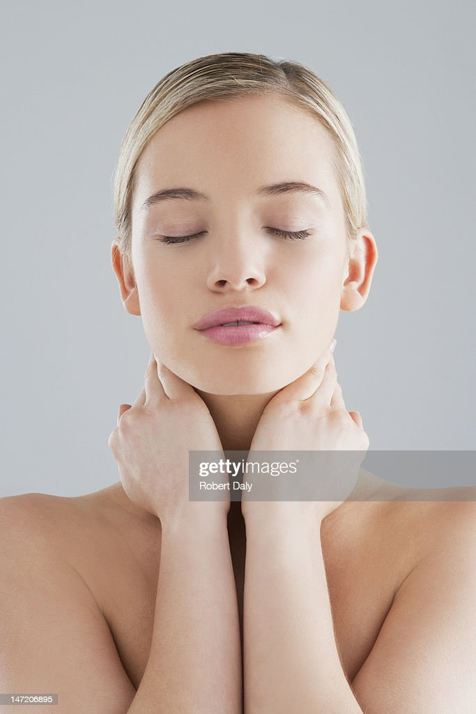 Woman with eyes closed and hands on neck : Stock Photo
