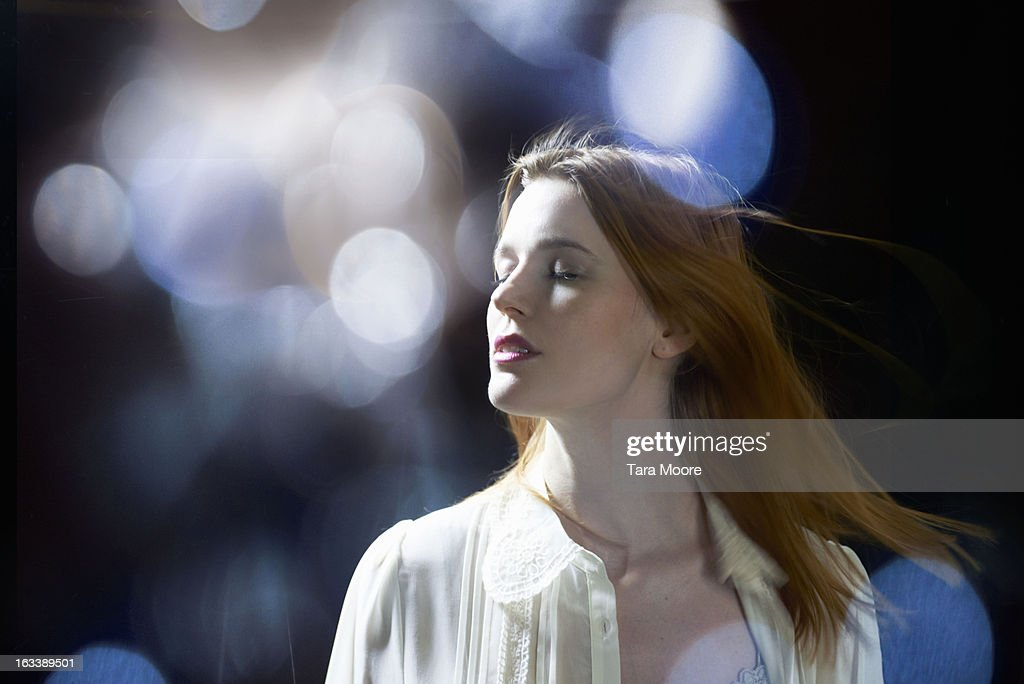 woman with eyes closed dreaming with lens flare : Stock Photo