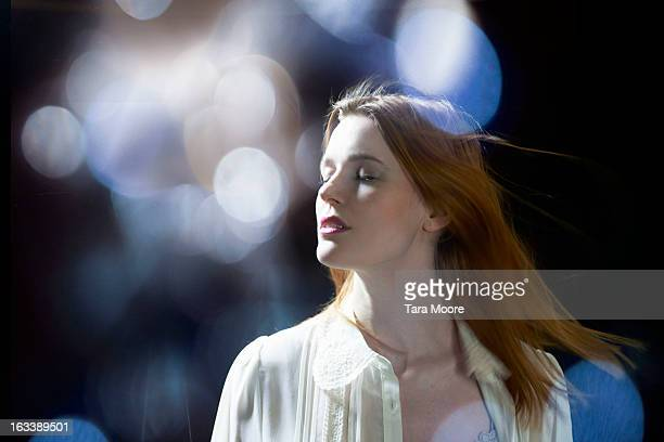 woman with eyes closed dreaming with lens flare