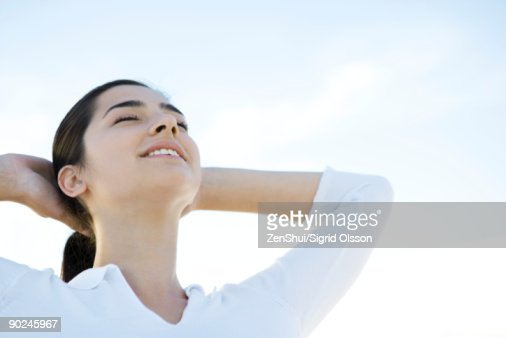 Woman with eyes closed, hands behind head