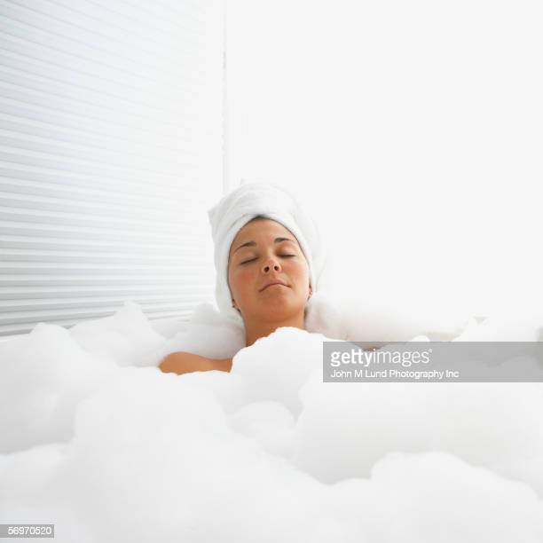Woman with eyes closed in bubble bath with towel on head