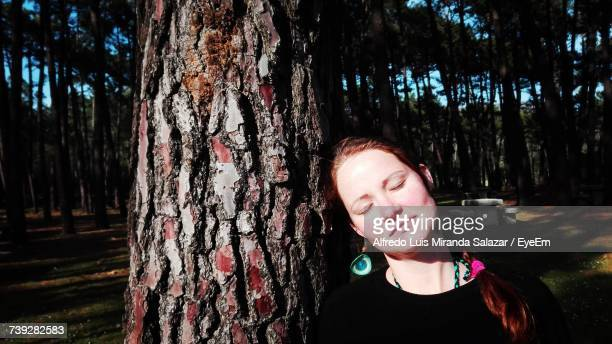 Woman With Eyes Closed Leaning On Tree Trunk