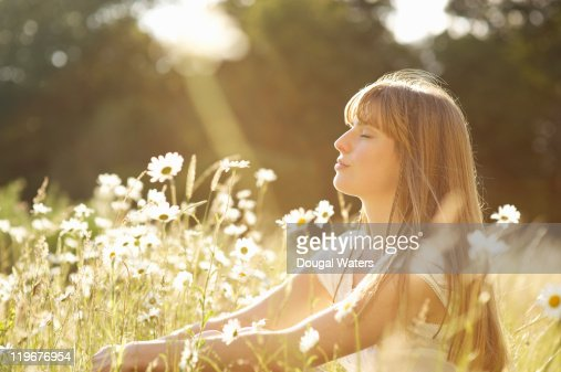 Woman with eyes closed sitting in meadow. : Stock Photo