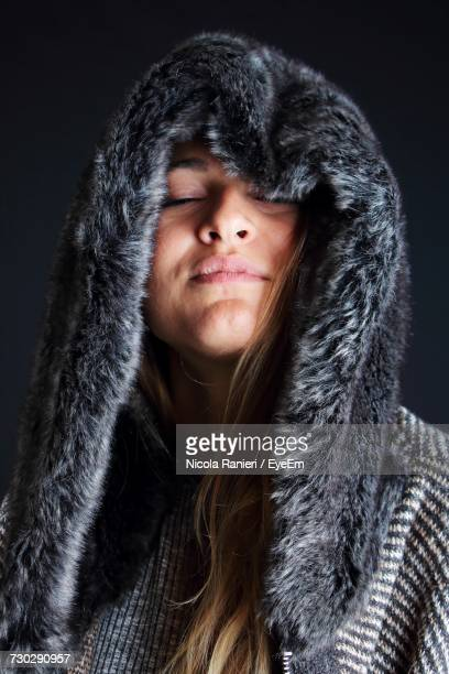 Woman With Eyes Closed Wearing Fur Coat Against Black Background