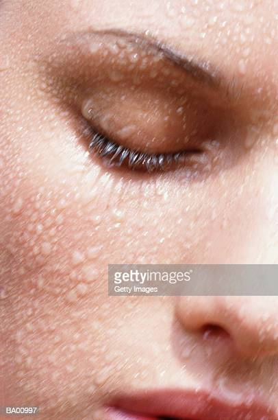 Woman with eyes closed with water on face, close-up