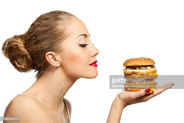 Woman with eyes shut and hamburger held out in her hand