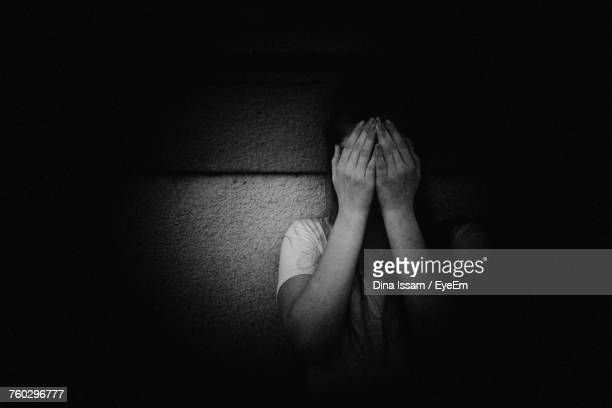 Woman With Face Covered By Hands Against Wall