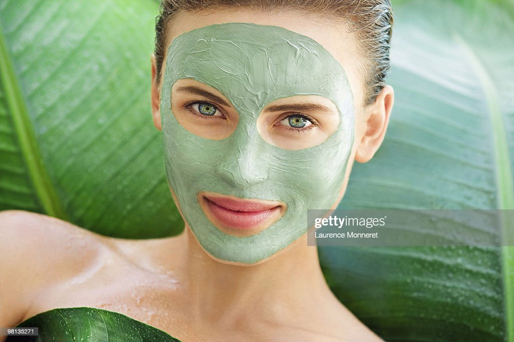 Woman with face green mud mask among big leaves