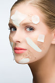 Woman with face mask and face scrub on her face